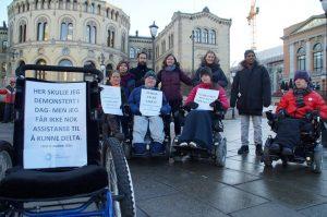 Flere mennesker foran stortinget. I forkant en tom rullestol med plakat med teksten: Her skulle jeg ha demonstrert i dag, men jeg får ikke nok assistase til å delta