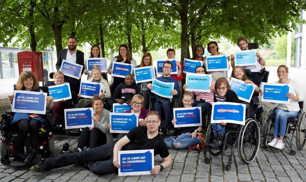 """Gruppe av medlemmer i NHFU der alle holder en liten plakat med tekst som """"Jeg vil kjempe mot all diskriminering. Vil du?"""""""